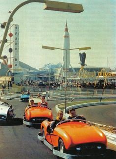 Disneyland Tomorrowland guests race in fully-bumpered 1955-1958 cars around the Autopia track (sans center rail) as the TWA Moonliner and Space Bar sign loom beyond the Richfield Eagle.