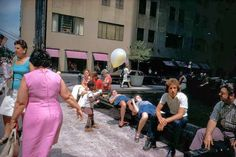 Image by Joel Meyerowitz. I think its really cool how the ladies pink dress matches the pink shade clothes on the store in the background of the image. i think the playfulness of the pink color works well with the child holding the balloon.