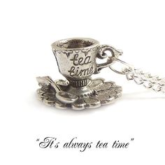 Tea cup necklace Alice in Wonderland necklace It's by LunarraStar  --  The silver plated teacup charm is intricately detailed, you can see hearts round the rim of the cup, the words tea time are inscribed on its side and it has it's own little spoon and saucer.