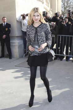 Clemence Poesy in a Chanel tweed jacket, gray top, and flared skirt at the Chanel Fall 2011 Fashion Week in Paris