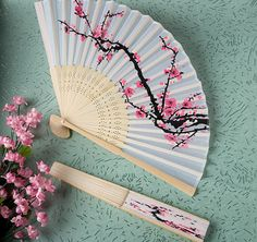 The Cherry Blossom Silk Folding Fans are the perfect accessory for that summer wedding or special event!  Your guests will appreciate its beauty and usefulness.  Each fan beautifully displays a cherry blossom branch (the traditional symbol of true love) in a traditional pink and black design.  Has an intricately carved light wood collapsible ribbing structure and is compact when folded and a breath of fresh air when opened!  Each fan is packaged in a white box.