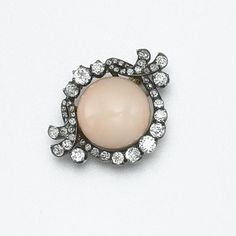 CORAL AND DIAMOND BROOCH, CIRCA 1870 Set with a button-shaped coral cabochon measuring approximately 15.8 by 15.5 mm., within a frame of 50 old European-cut and old-mine diamonds weighing approximately 1.25 carats, mounted in silver and gold.