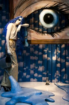 The eyes get drawn from the floor to the mannequin to the eye.  It starts at the floor because there is open space and a place where your eyes first rest at, then it moves to the mannequin and follows the arm to the eye picture.  I love the backdrop and the use of blues and the texture of the pleats.  This is more like a work of art then selling of clothing but for that very reason it as a window display still works.