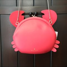 """Kate spade make a splash crab crossbody purse  • 100% Authentic • Kate Spade frame handbag crab • Black eyes/snap closure • Geranium pink leather • Gold chain crossbody strap • Inside slash pocket • Navy signature fabric lining • New with tag • Crab is approximately 8"""" x 9"""". Chain strap drop is about 20"""" kate spade Bags Crossbody Bags"""