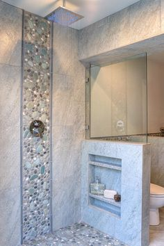 This master shower features a detail stripe of river rock that travels down the wall to the floor, defining the perimeter of the open shower. An overhead rain shower head completes the high-end spa feel.