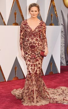 2016 Oscars: Chrissy Teigen is glowing in a red long sleeve Marchesa gown with a train. She is absolutely radiant!