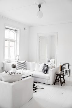 white wooden floor * white walls / sofa / coffee table / hanginglamp * black sidetable / cushions * home * livingroom * interior * decor * style