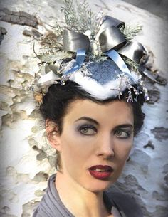 WINTER FROST HAT A cameo nestles into satin ribbon of pewter, icy sprigs and cedar upon a fabulous fur-trimmed damask cap. Slate blue and silver.  The Sisters Brimm, $199.95