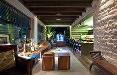 Acoplada ao living (26 m²) por meio da grande bancada de Silestone que serve de mesa e apoia o cooktop, a cozinha (9 m²; à dir.) destaca-se pelo revestimento em porcelanto cortado em listras e pelos móveis de design como as cadeiras Louis Ghost, do designer Philippe Starck. A proposta do arquiteto Ricardo Rossi trabalhou a formatação da cozinha em contraponto ao estilo mais rústico da sala, uma vez que as áreas não têm separação