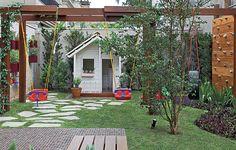 Um quintal pra filho nenhum botar defeito: além dos balanços, ao fundo, uma casinha de boneca tem telhas e piso de madeira de verdade. Do lado direito, ainda há uma parede de escalada que garante a diversão da criançada