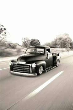 Chopped Advance Design pickup in satin black rolling down the highway.