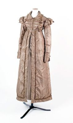 1818-1820.  A fawn silk carriage dress pelisse, with frogged front, Cap sleeves over long sleeves. Tasselled decorations.