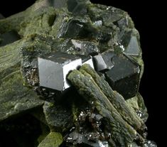 Epidote with Grossular Garnet, near Diakon, Kayes Region, Mali. Large green epidote crystals up to 40 mm long with dodecahedral smooth brown grossular garnet crystals up to 14 mm across embedded in areas of the epidote. The epidote crystals have surfaces composed of many smaller crystal faces.  Overall Size:8x7x5 cm.  Crystals:2-40 mm