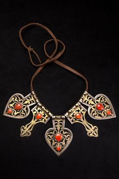 Turkmenistan | Necklace; five Asyk pendants fixed on a leather ribbon. Gold and silver pendant adorned with red cornaline and an intricate fire-gilded pattern.  From the Tekke people | ca. end of the 19th to beginning of the 20th century. | 2,562$