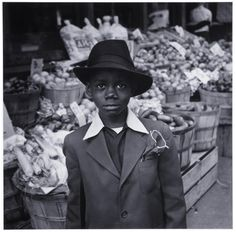 A boy wearing Sunday best next to a vegetable stand in Pittsburgh's Hill District neighborhood [1951]