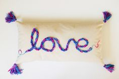 flax & twine: Finish Fifty: DIY Tasseled Love Pillow. Don't like the tassels but I love the pillow/ finger knitted words.