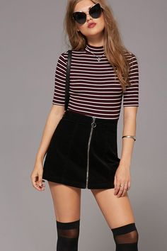 A corduroy mini skirt featuring a slight A-line silhouette and a zippered front.
