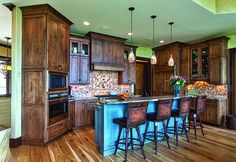 The oak kitchen island — stained in a custom-mix blue, glazed and distressed — anchors this kitchen in Walnut Cove. Blown glass pendant ligh...