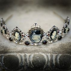 Where the world of shadows meets magic and beauty. Gothic-inspired headpiece incorporates a series of black and ivory cameos surrounded by genuine marcasite and garnet. Garnet cabachons set in marcasite settings line the base. Glass pearls and Swarovski rhinestones in dark red, gray, amethyst and aurora borealis add incredible sparkle to this stunning tiara.