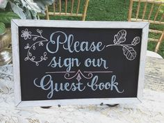 Hand-drawn chalkboard sign for wedding guest book table
