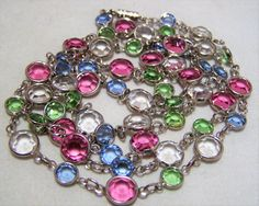 Vintage open back faceted glass rhinestone 35 inch necklace Round faceted pastel stones, pink, green, blue and crystal glass Stones alternate sizes 6 and 9 mm Silver tone setting, screw barrel clasp Very good vintage condition, shows no wear International buyers welcome, shipping is automatically combined, overcharges are refunded Flat rate priority shipping is optional 10417  Credit cards and Paypal accepted.  Want to see more great necklaces? Click here: https://www.etsy.com/...