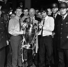 Manchester United manager Matt Busby (centre) holding the European Cup trophy with players Pat Crerand (left) and George Best, at Euston Sta...