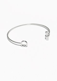 Thin and elegant metal cuff featuring a shiny brass bar.