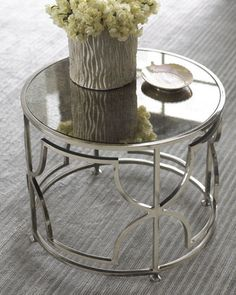 "Iron Side Table  Iron Side Table    A brilliant nickel-plated finish combines with an antiqued-mirrored top and a modern geometric design. 20""Dia. x 16""T.  $600"