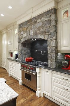 Stone surrounds gas cooking stove in this traditional white #kitchen