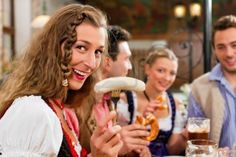 group of young men and women in traditional Bavarian Tracht having a breakfast with white veal sausage, pretzel, and beer Stock Photo