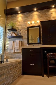 stone wall in bathroom, dark wood cabinets