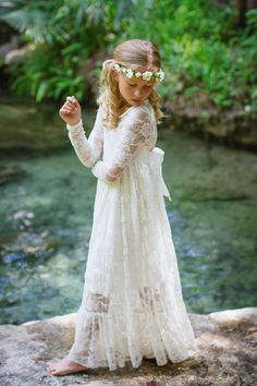 The Ultimate Chic Floor Length Ivory Lace Dress. Made of high quality stretch floral ivory lace. Paired with satin attached to create the perfect bow on the back. Full length sleeves. Underlay creates a sweetheart design on the top. Perfect dress for twirling and dancing. Formal for a flower girl,