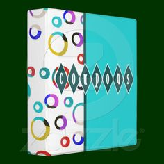 "Irregular hoops in color block shades of yellow, red, blue, purple and turquoise against a white background wrap around the spine of this retro turquoise coupon organizer binder. The word ""coupons"" with each letter in a diamond shape adds to the retro feel"