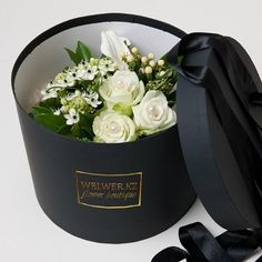 A lovely white flower bouquet in a round black box with a satin bow♡