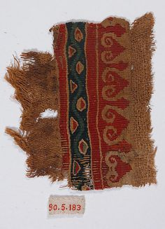 5 c. Fragment of a Tunic. Wool, linen; plain weave, tapestry weave. Dimensions: 3 3/8 in. high 2 3/4 in. wide (8.5 cm high 7 cm wide). Accession Number: 90.5.183