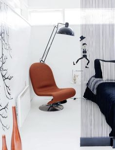 A modern leather chair in a white bedroom with industrial floor lamp