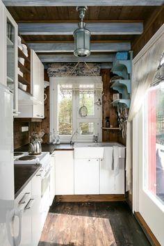 Vaaleat kaapistot, keraaminen allas, kattoparrut, tummat puuseinät ja lattia sekä ihanat yksityiskohdat tekevät mökin keittiöstä todella kodikkaan ja maalaisromanttisen.