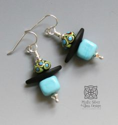 "Flamework glass lantern earrings. Casual, bright colors -Light Blue & Lime Green. The square bottom bead is hollow, so the earrings are lightweight and comfortably wearable all day long. Colored glass beads are crafted in our studio from a molten state in a 1200 degree torch flame. Earrings measure approximately 1 1/2 "" long and 1/2"" wide. Sterling silver wire & beads.One-of-a-kind.Free shipping in continental USA. Additional shipping charges for International deliveries TBD. Customers r Light Colors, Light Blue, Contrast Lighting, Glass Design, Colored Glass, Lanterns, Glass Beads, Lime, Drop Earrings"
