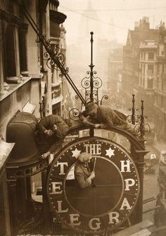 Workmen dismantle the clock which hangs outside the Daily Telegraph building at 135 to 141, Fleet Street, London, 1930