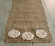 For sale on etsy but i feel like would be a great DIY project! A beautiful 72 inch burlap table runner, adorned with three cotton rosettes on each end. No worries about unraveling, the runner is finished with a nearly invisble stitch around the edges.