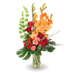 A contemporary funeral arrangement with a bold color palette, designed with coral gladiolas, bells of Ireland, tropical leaves, red roses, carnations, and spiral eucalyptus.