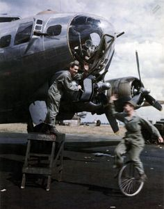 """""""T/Sgt Charles A. Barbier of Wallace, La., checking gun mount bolt on a B-17, waves to M/Sgt. George Grose of Tallahassee, Fla., as he rides by on unicycle."""""""