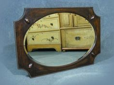 This is a superb quality antique oak framed mirror  Fabulous oak frame with cut away corners, beading and oval button detail   Beveled edge mirror surface  Hanging chain and original wooden back  Beautiful grain and patina to  the oak frame  Measures approx  56 cms High   84 cms Wide