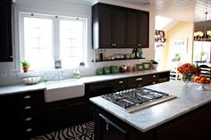 Love the dark cabinets, white marble countertops and backsplashes.