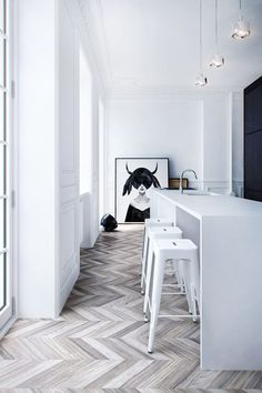 ChicDecó | Minimalist black and white kitchen with tolix stools and black and white print. Herringbone wooden floor
