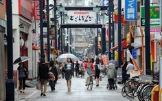 Pedestrians walk through the Togoshi shopping district in Tokyo - Toshifumi Kitamura/AFP/Getty Images