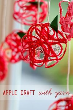 A yarn apple craft for kids to make in the fall, great for using up leftover yarn.