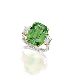 TSAVORITE GARNET AND DIAMOND RING | Centring on a cushion-shaped tsavorite garnet weighing approximately 10.76 carats, flanked on each side by a trapeze-shaped diamond together weighing approximately 1.18 carats, mounted in platinum and 18 karat yellow gold. | Sotheby's