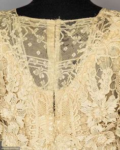IRISH CROCHET LACE EVENING GOWN, c. 1905. 1 piece trained princess line gown, short sleeves, machine lace neck insert, skirt lace worked in vertical rows of small motif dense bands alternating w/ rows of large floral designs. Detail