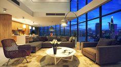 """Thiết kế """"Penthouse Comfort""""  Bao trùm căn hộ áp mái Penthouse Comfort là màu trắng thư giãn, ngọt ngào. Thiết kế nội thất phòng khách đương đại thể hiện rõ qua bộ ghế salon hình khối và chiếc đèn đứng uốn cong."""